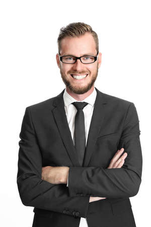 A successful and happy executive businessman wearing glasses, black suit and tie, and a white collared shirt with his arms crossed standing against white background Foto de archivo