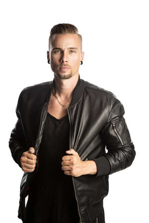 Attractive young bearded man wearing a trendy black leather jacket and black shirt looking angry at the camera with both hands holding his jacket and standing against white background.