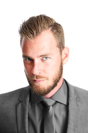 An attractive bearded male executive looking serious towards the camera wearing a black coat and tie.