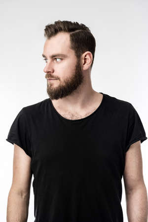 Nordic man with a beard wearing a black shirt with his hands on his sides looking sideways. Grey background.