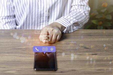 お問い合わせまたはカスタマーサポートのホットラインの人が接続します。(電子メール、電話、メール)アイコンを持つ携帯電話を使用してビジネスマン。 写真素材