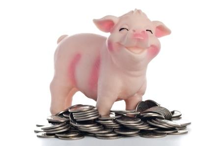 Ein Sparschwein gegenüber dem weißen Hintergrund in einem Haufen von Münzen