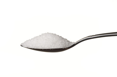 Sugar in a spoon isolated over white background photo