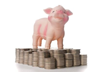 Happy piggy bank standing on stacks of coins photo