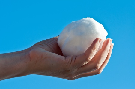 Female holding a snow ball in sunlight with blue sky as background photo