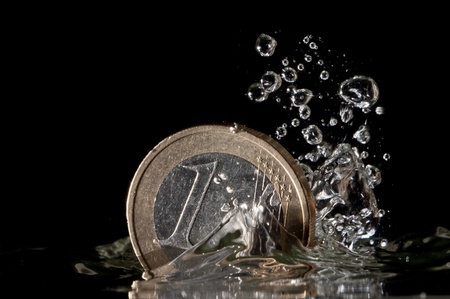 One euro coin splashing in to the water on black background