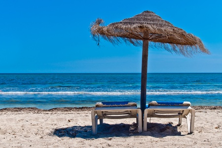 Two loungers under sun umbrella at the beach Stock Photo