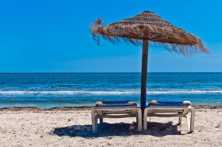 Zwei Liegestühle unter Sonnenschirmen am Strand