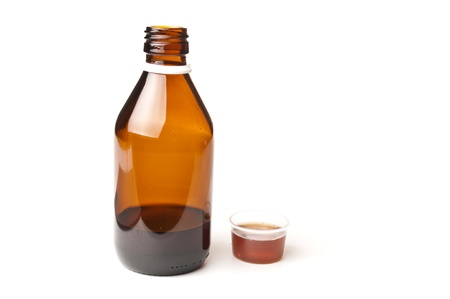 Cough medicine in a glass bottle with dosage cup filled