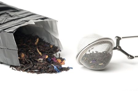 Tea in bag and tea strainer over white background photo