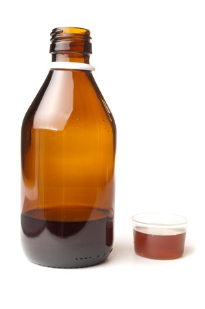 Cough syrup in a bottle with dosage cup for drinking filled up photo