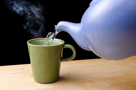 Pouring steaming hot tea from a blue tea pot in to a green cup Standard-Bild