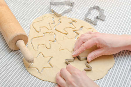 Womans hands baking Christmas cookies on a table photo