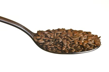 Flax seeds in a spoon isolated over white background photo