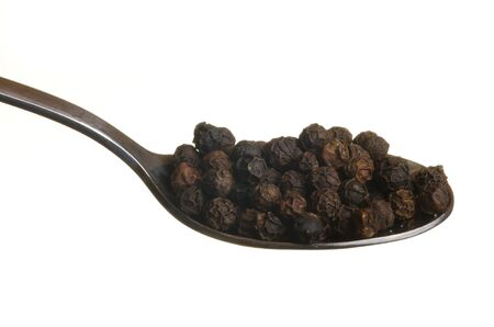 Black pepper in a spoon isolated over white background photo