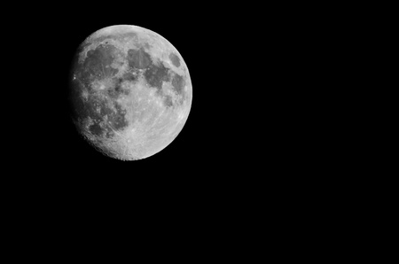 not full: The moon, not full, seen from earth isolated over black