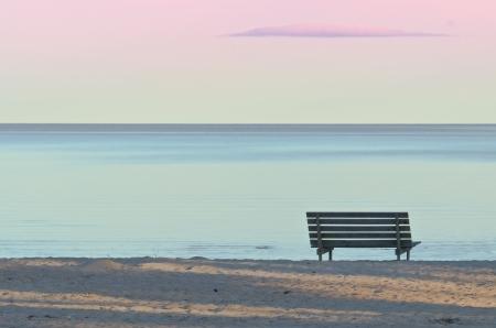 horizonte: Bench en una playa de arena en la noche