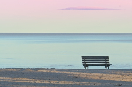 serenity: Bench on a sandy beach in the evening