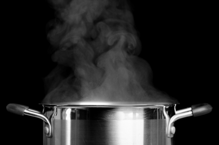 Boiling water in casserole over black background Stock Photo