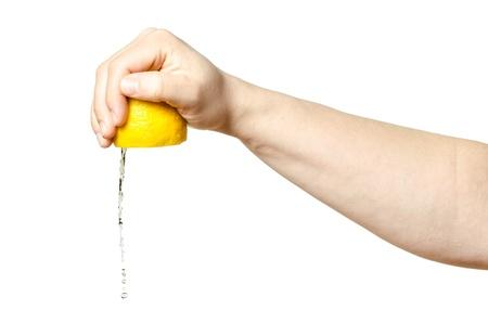 Hand squeezing lemon with juice isolated on white background Stock Photo