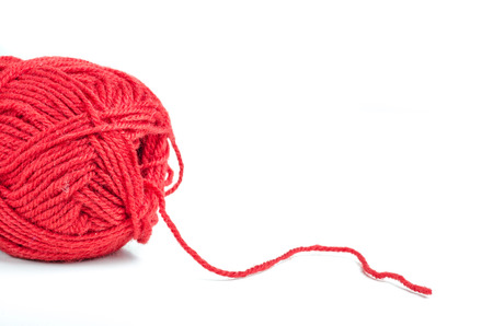 Red woolen thread from a yarn on white background photo