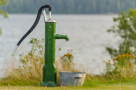Old water pump in front of a lake in summertime Фото со стока