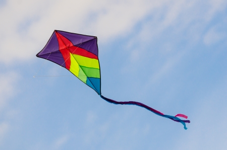 Colorful kite flying in the sky with clouds in background