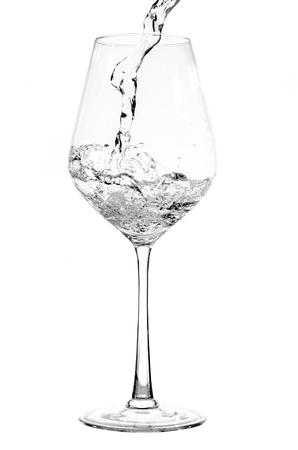 Gießen reines Wasser in ein Glas isoliert auf weiß