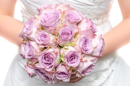 Bride in white dress holding purple wedding bouquet Standard-Bild