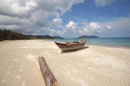 con dao: Boat and Driftwood, Con Dao, Vietnam Stock Photo