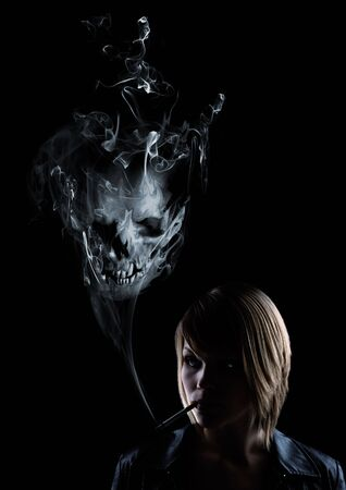 young women smokes and in the smoke appears a skull Stock Photo