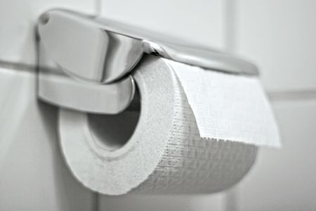 Toiletpaper on a holder hanging on the wall Stock Photo