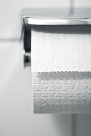 lav: Toiletpaper on a holder hanging on the wall Stock Photo