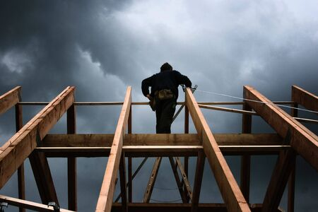 roof framework: roofer on a roof framework in front of a cloudy sky Stock Photo