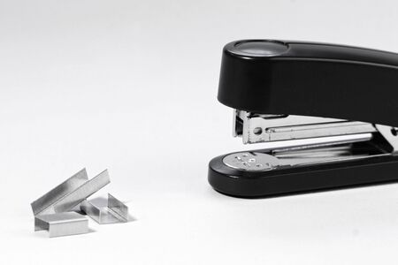 black stapler and staples isolated on white background photo