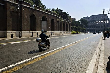 dei: scooter drives towards the colloseum in Rome on the via dei fori imperiali