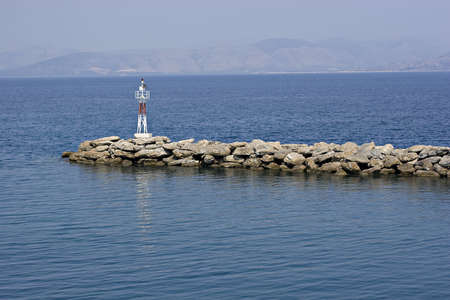 bulwark: small lighthouse on a breakwater in the the Aegean Stock Photo