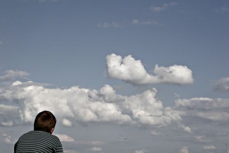 dramatically: boy is looking into a dramatically cloudy sky Stock Photo