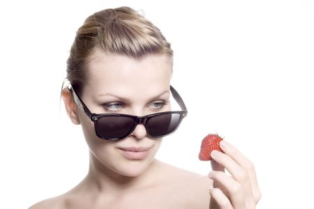 beautiful blonde girl with sunglasses looks at a strawberry photo