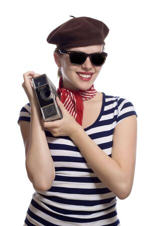 beautiful girl with red bandana, beret and striped shirt in a classic 60s french look holding a vintage 8mm substandard camera photo