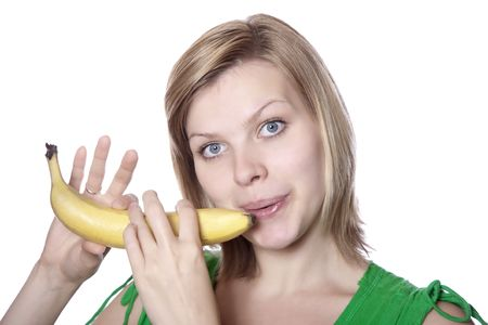beautiful blonde young girl playing on a banana like a flute, isolated on white photo
