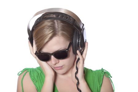 beautiful girl in a green dress and vintage sunglasses listening to music with big headphones, isolated on white photo