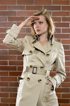 young women in a trenchcoat is on a lookout Stock Photo