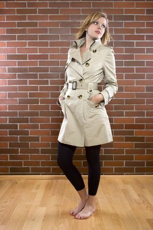 beautiful young women is posing in a trenchcoat