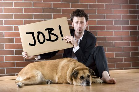 desperate businessman sits with a dog on the floor and holds a Need Job sign