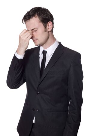 businessman in a black suit with headache isolated on white photo