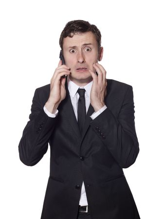 scared man: afraid looking businessman with a phone in a black suite isolated on white