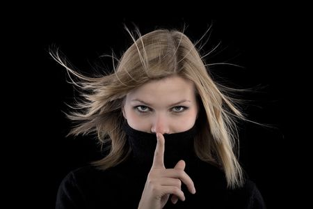 young beautiful blonde girl in a black turtleneck is requesting silence. photo