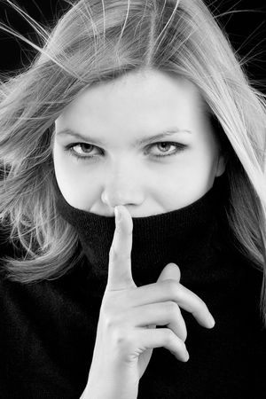 young beautiful blonde girl in a black turtleneck is requesting silence. black and white image photo