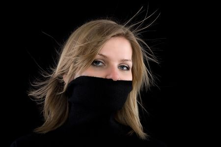 turtleneck: beautiful blonde girl covers her mouth with a black turtleneck on black background